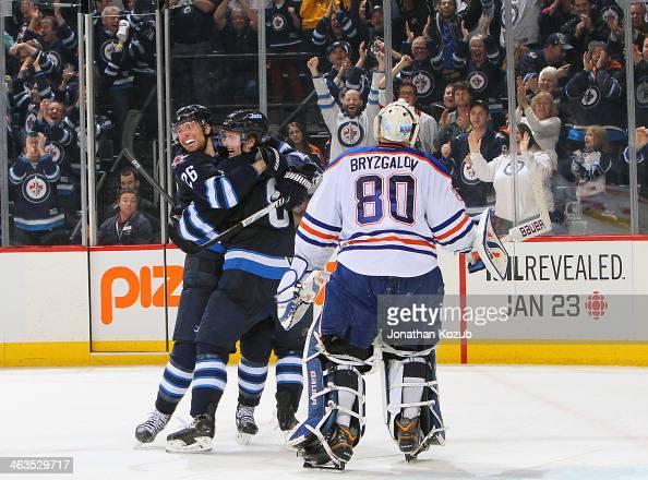 Goaltender Ilya Bryzgalov of the Edmonton Oilers skates off the iec as Blake Wheeler and Jacob Trouba of the Winnipeg Jets celebrate an overtime goal...