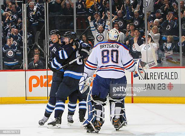 Goaltender Ilya Bryzgalov of the Edmonton Oilers skates off the iec as Blake Wheeler and Jacob Trouba of the Winnipeg Jets celebrate an overtime goal...