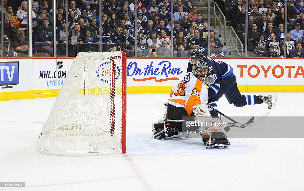 Goaltender <a gi-track='captionPersonalityLinkClicked' href=/galleries/search?phrase=Ilya+Bryzgalov&family=editorial&specificpeople=2285430 ng-click='$event.stopPropagation()'>Ilya Bryzgalov</a> #30 of the Philadelphia Flyers deflects a shot by <a gi-track='captionPersonalityLinkClicked' href=/galleries/search?phrase=Evander+Kane&family=editorial&specificpeople=4303789 ng-click='$event.stopPropagation()'>Evander Kane</a> #9 of the Winnipeg Jets to the corner boards during second period action at the MTS Centre on February 12, 2013 in Winnipeg, Manitoba, Canada.