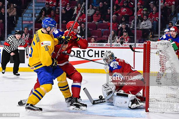Goaltender Ilya Samsonov of Team Russia makes a stick save while teammate Grigori Dronov battles for position with Lias Andersson of Team Sweden...