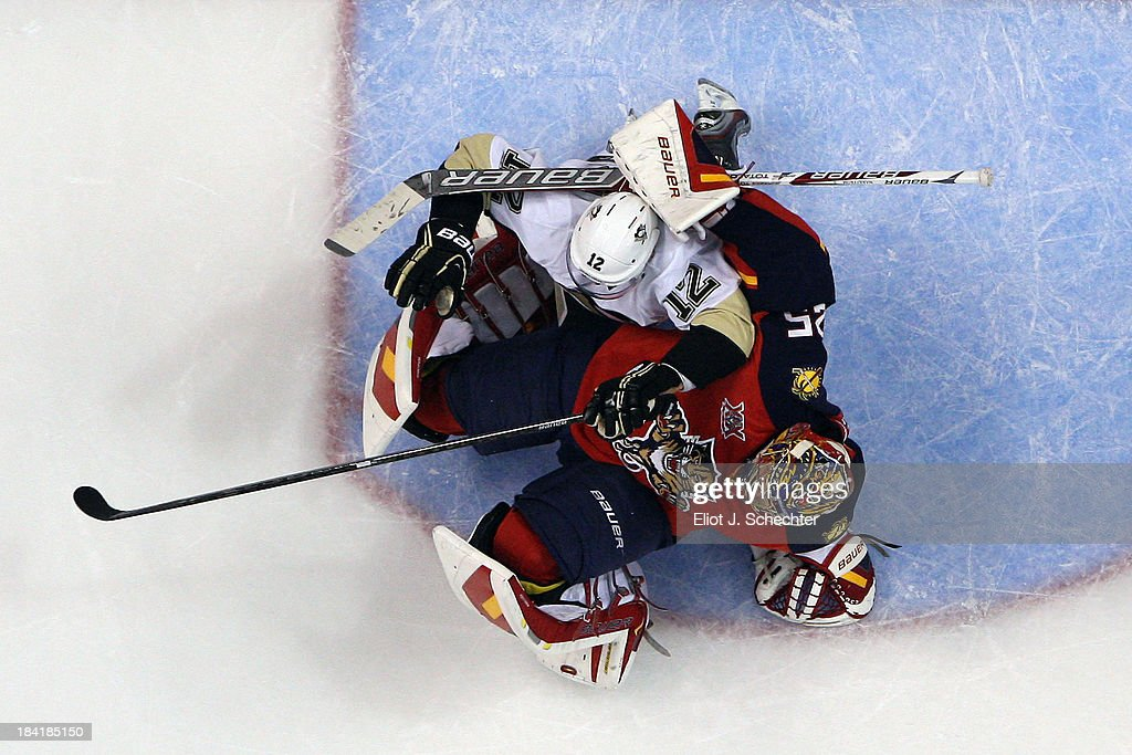 Goaltender <a gi-track='captionPersonalityLinkClicked' href=/galleries/search?phrase=Jacob+Markstrom&family=editorial&specificpeople=5370948 ng-click='$event.stopPropagation()'>Jacob Markstrom</a> #25 of the Florida Panthers defends the net against <a gi-track='captionPersonalityLinkClicked' href=/galleries/search?phrase=Chuck+Kobasew&family=editorial&specificpeople=208995 ng-click='$event.stopPropagation()'>Chuck Kobasew</a> #12 of the Pittsburgh Penguins at the BB&T Center on October 11, 2013 in Sunrise, Florida.