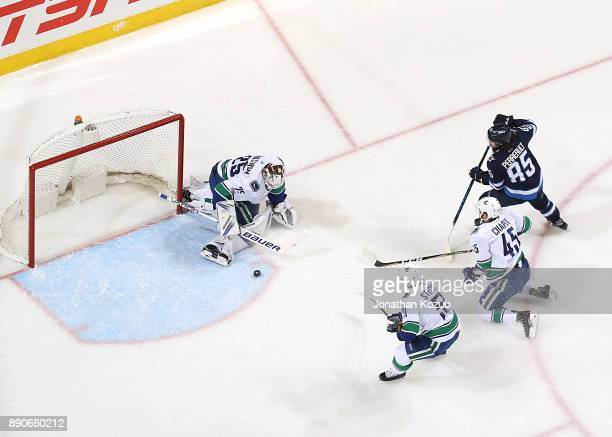 Goaltender Jacob Markstrom of the Vancouver Canucks makes a pad save as teammates Troy Stecher Michael Chaput and Mathieu Perreault of the Winnipeg...