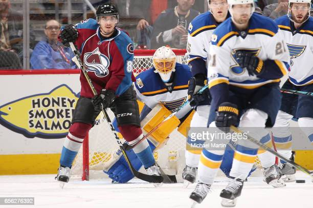Goaltender Jake Allen of the St Louis Blues watches an incoming shot next to Matt Nieto of the Colorado Avalanche at the Pepsi Center on March 21...