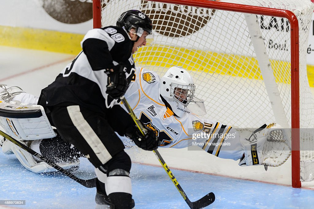 Goaltender James Povall of the Victoriaville Tigres dives to make a save in front of Miguel Picard of the BlainvilleBoisbriand Armada during the...