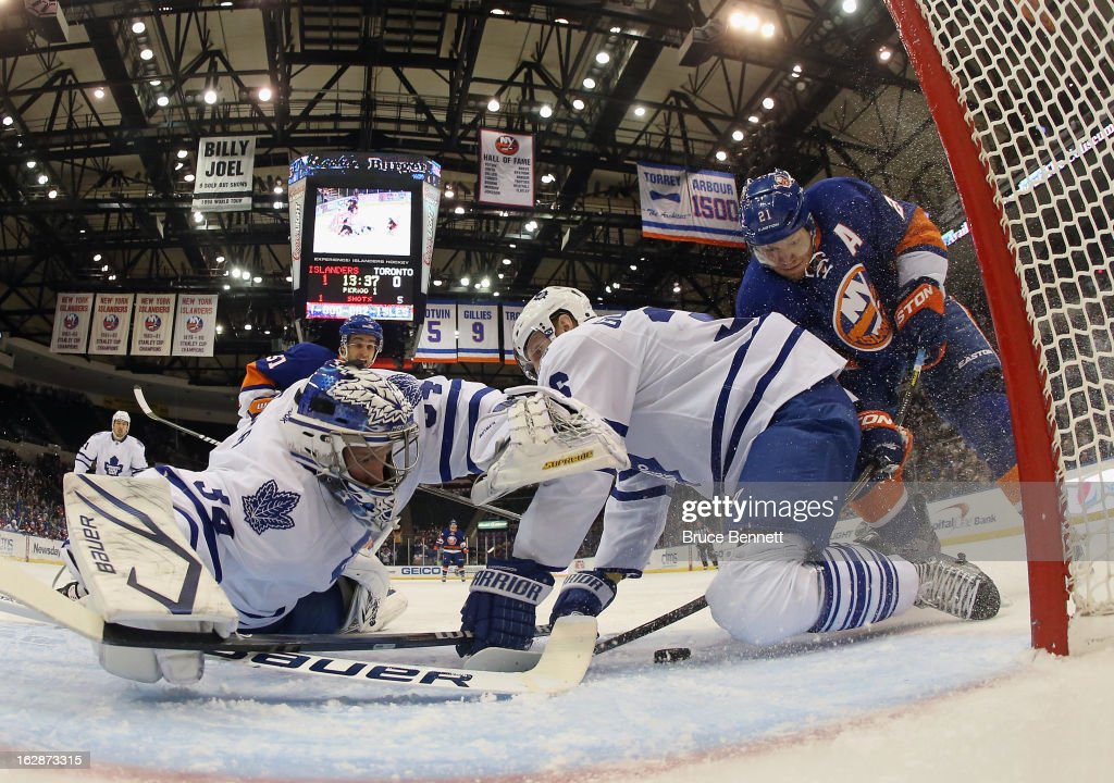 Goaltender James Reimer #34 and defenseman <a gi-track='captionPersonalityLinkClicked' href=/galleries/search?phrase=Carl+Gunnarsson&family=editorial&specificpeople=5557315 ng-click='$event.stopPropagation()'>Carl Gunnarsson</a> #36 of the Toronto Maple Leafs manage to stop <a gi-track='captionPersonalityLinkClicked' href=/galleries/search?phrase=Kyle+Okposo&family=editorial&specificpeople=540469 ng-click='$event.stopPropagation()'>Kyle Okposo</a> #21 of the New York Islanders in the first period at the Nassau Veterans Memorial Coliseum on February 28, 2013 in Uniondale, New York.