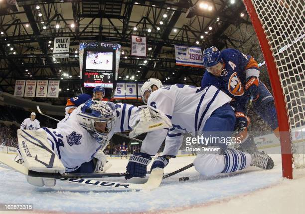 Goaltender James Reimer and defenseman Carl Gunnarsson of the Toronto Maple Leafs manage to stop Kyle Okposo of the New York Islanders in the first...