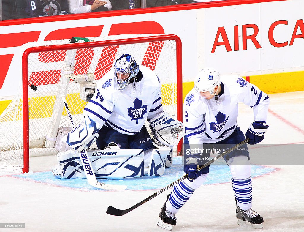 Goaltender James Reimer #34 and <a gi-track='captionPersonalityLinkClicked' href=/galleries/search?phrase=Luke+Schenn&family=editorial&specificpeople=4254202 ng-click='$event.stopPropagation()'>Luke Schenn</a> #2 of the Toronto Maple Leafs react as the puck goes into the net during second period action against the Winnipeg Jets at the MTS Centre on December 31, 2011 in Winnipeg, Manitoba, Canada.