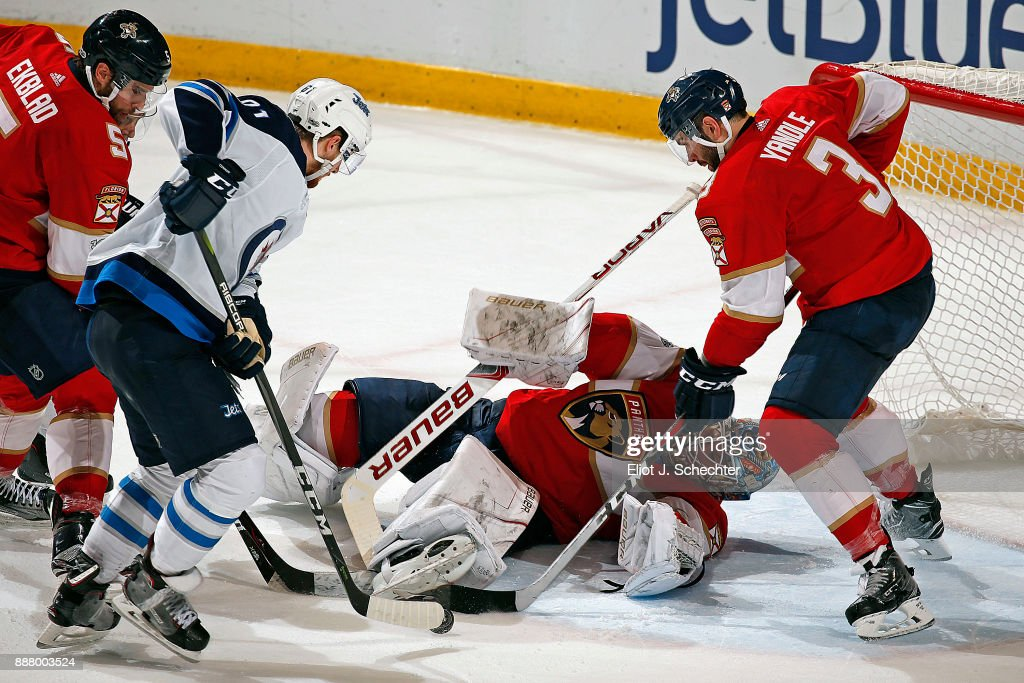 Goaltender James Reimer #34 of the Florida Panthers defends the net with the help of teammate Keith Yandle #3 against Kyle Connor #81 of the Winnipeg Jets at the BB&T Center on December 7, 2017 in Sunrise, Florida.