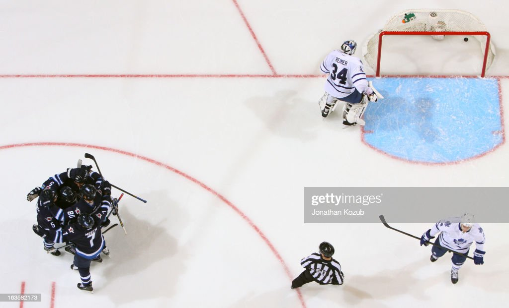 Goaltender James Reimer #34 of the Toronto Maple Leafs looks at the puck in the net as Winnipeg Jets players celebrate behind him during second period action at the MTS Centre on March 12, 2013 in Winnipeg, Manitoba, Canada.