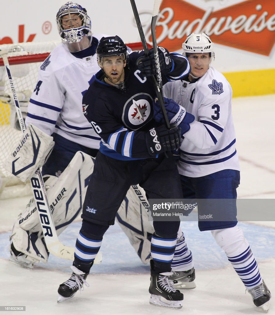 Goaltender James Reimer #34 of the Toronto Maple Leafs tries to look around the two captains, <a gi-track='captionPersonalityLinkClicked' href=/galleries/search?phrase=Andrew+Ladd&family=editorial&specificpeople=228452 ng-click='$event.stopPropagation()'>Andrew Ladd</a> #16 of the Winnipeg Jets and <a gi-track='captionPersonalityLinkClicked' href=/galleries/search?phrase=Dion+Phaneuf&family=editorial&specificpeople=545455 ng-click='$event.stopPropagation()'>Dion Phaneuf</a> #3 of the Toronto Maple Leafs as they push each other in front of his net in NHL action on February 7, 2013 at the MTS Centre in Winnipeg, Manitoba, Canada.