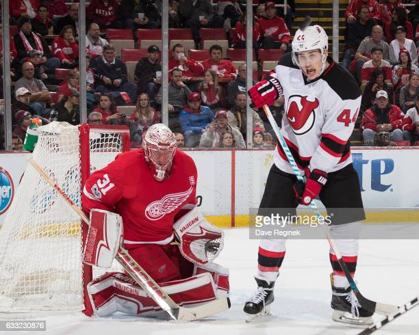 Goaltender Jared Coreau of the Detroit Red Wings follows the puck as Miles Wood of the New Jersey Devils looks for the rebound during an NHL game at...