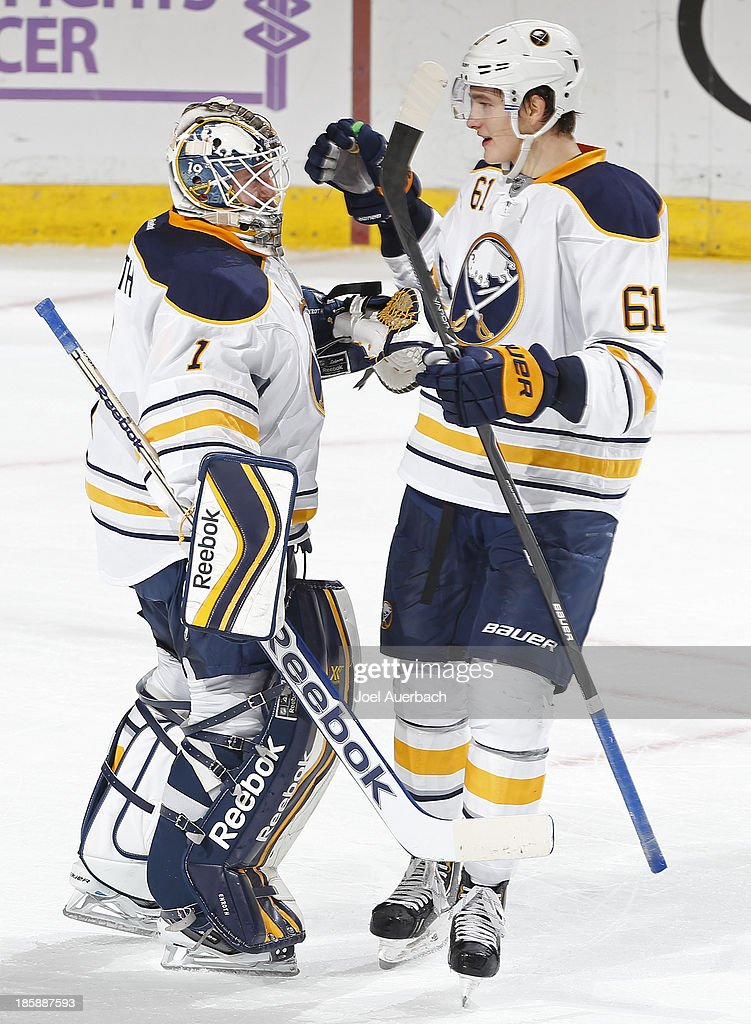 Goaltender <a gi-track='captionPersonalityLinkClicked' href=/galleries/search?phrase=Jhonas+Enroth&family=editorial&specificpeople=570456 ng-click='$event.stopPropagation()'>Jhonas Enroth</a> #1 is congratulated by <a gi-track='captionPersonalityLinkClicked' href=/galleries/search?phrase=Nikita+Zadorov&family=editorial&specificpeople=9784875 ng-click='$event.stopPropagation()'>Nikita Zadorov</a> #61 of the Buffalo Sabres after the game against the Florida Panthers at the BB&T Center on October 25, 2013 in Sunrise, Florida. The Sabres defeated the Panthers 3-1.