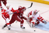 Goaltender Jimmy Howard of the Detroit Red Wings dives to make a save on Matthew Lombardi of the Phoenix Coyotes as Nicklas Lidstrom defends in the...