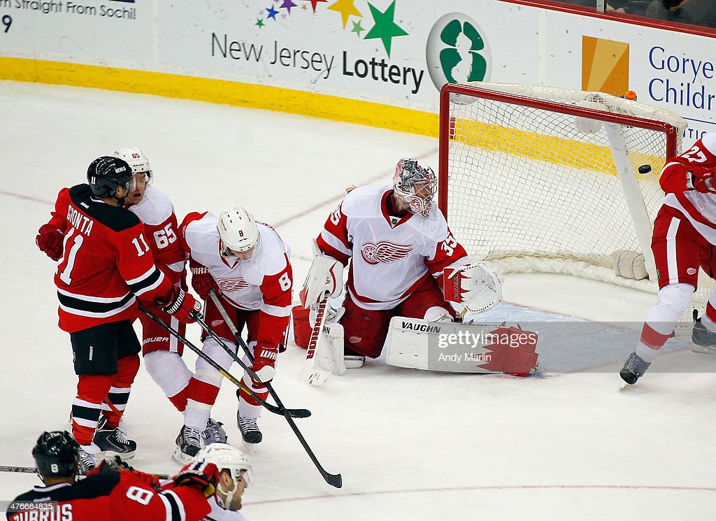 Goaltender Jimmy Howard of the Detroit Red Wings looks behind him at the puck in the net on the gamewinning goal by Stephen Gionta of the New Jersey...