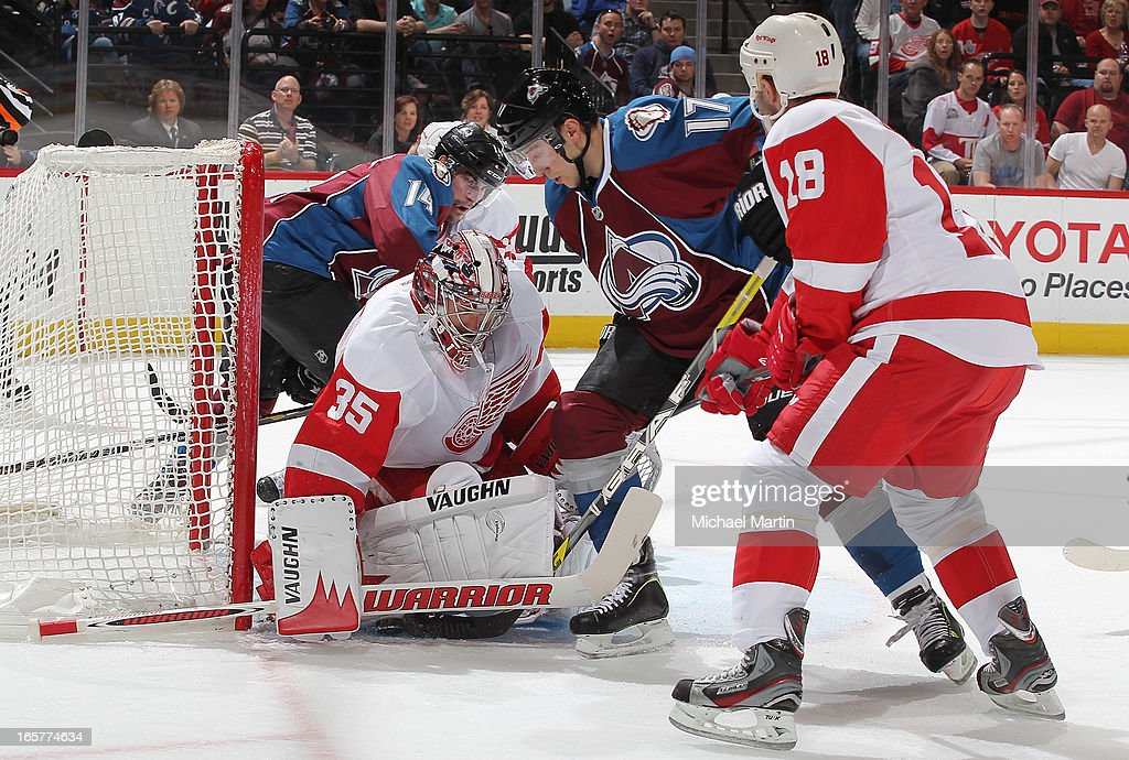 Goaltender <a gi-track='captionPersonalityLinkClicked' href=/galleries/search?phrase=Jimmy+Howard&family=editorial&specificpeople=2118637 ng-click='$event.stopPropagation()'>Jimmy Howard</a> #35 of the Detroit Red Wings makes a save against Aaron Palushaj #17 the Colorado Avalanche at the Pepsi Center on April 5, 2013 in Denver, Colorado.