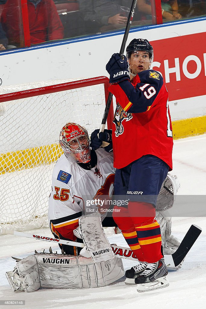 Goaltender Joey MacDonald #35 of the Calgary Flames defends the net against Scottie Upshall #19 of the Florida Panthers at the BB&T Center on April 4, 2014 in Sunrise, Florida.