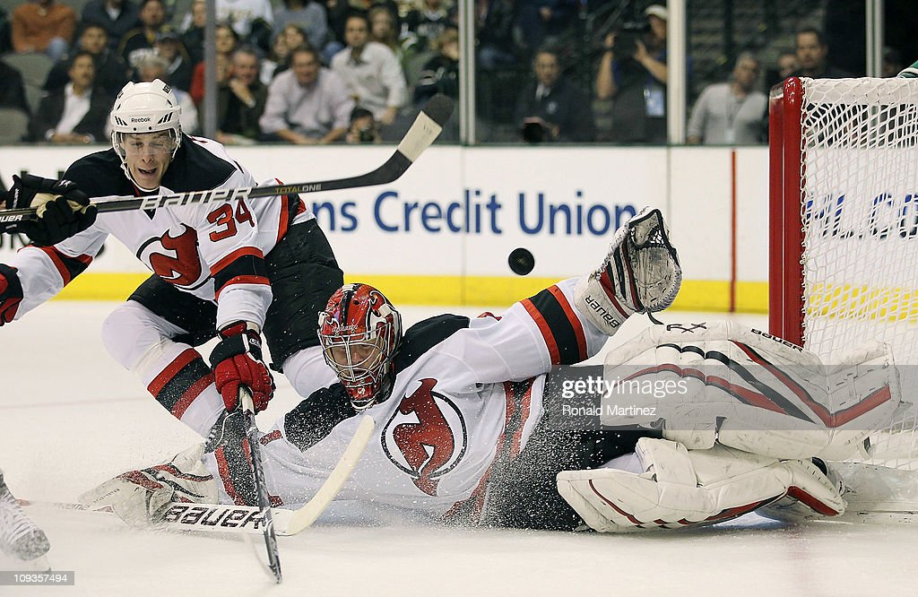 Goaltender Johan Hedberg of the New Jersey Devils makes a save against the Dallas Stars in front of Mark Fayne at American Airlines Center on...
