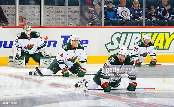 Goaltender John Curry Stu Bickel Justin Fontaine and Thomas Vanek of the Minnesota Wild stretch as they take part in the pregame warm up prior to NHL...