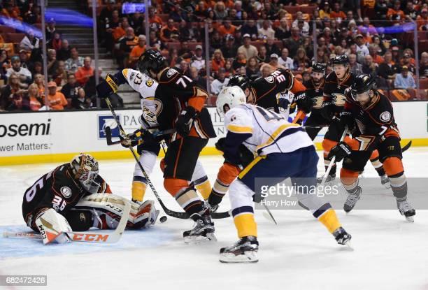 Goaltender John Gibson of the Anaheim Ducks makes a save as Colin Wilson of the Nashville Predators and Brandon Montour of the Anaheim Ducks vie for...