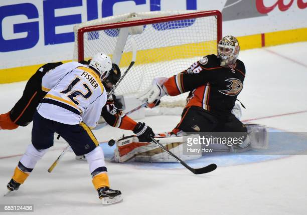 Goaltender John Gibson of the Anaheim Ducks makes a save in front of Mike Fisher of the Nashville Predators and Ryan Kesler in the third period of...