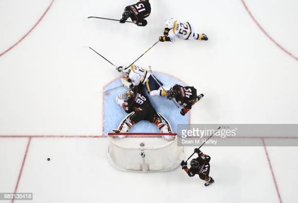 Goaltender John Gibson of the Anaheim Ducks sprawls on the ice as Rickard Rakell Ryan Getzlaf and Sami Vatanen help defend against the play of Mike...