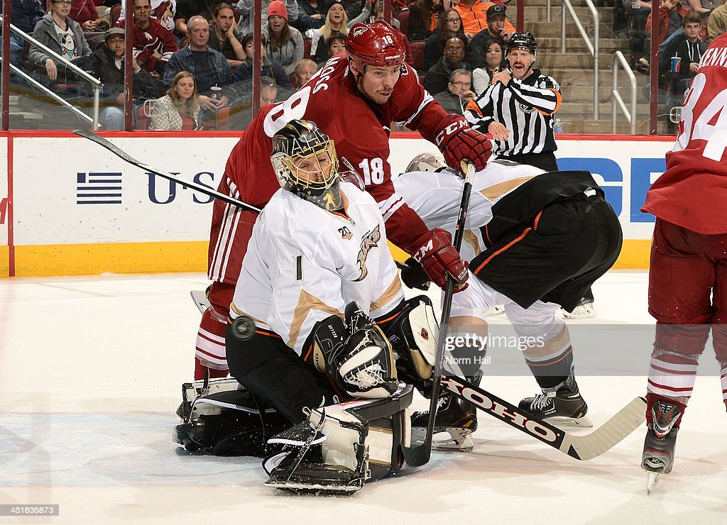 Goaltender <a gi-track='captionPersonalityLinkClicked' href=/galleries/search?phrase=Jonas+Hiller&family=editorial&specificpeople=743364 ng-click='$event.stopPropagation()'>Jonas Hiller</a> #1 of the Anaheim Ducks deflects the puck for a save as David Moss #18 of the Phoenix Coyotes reaches in to redirect during the second period at Jobing.com Arena on November 23, 2013 in Glendale, Arizona.