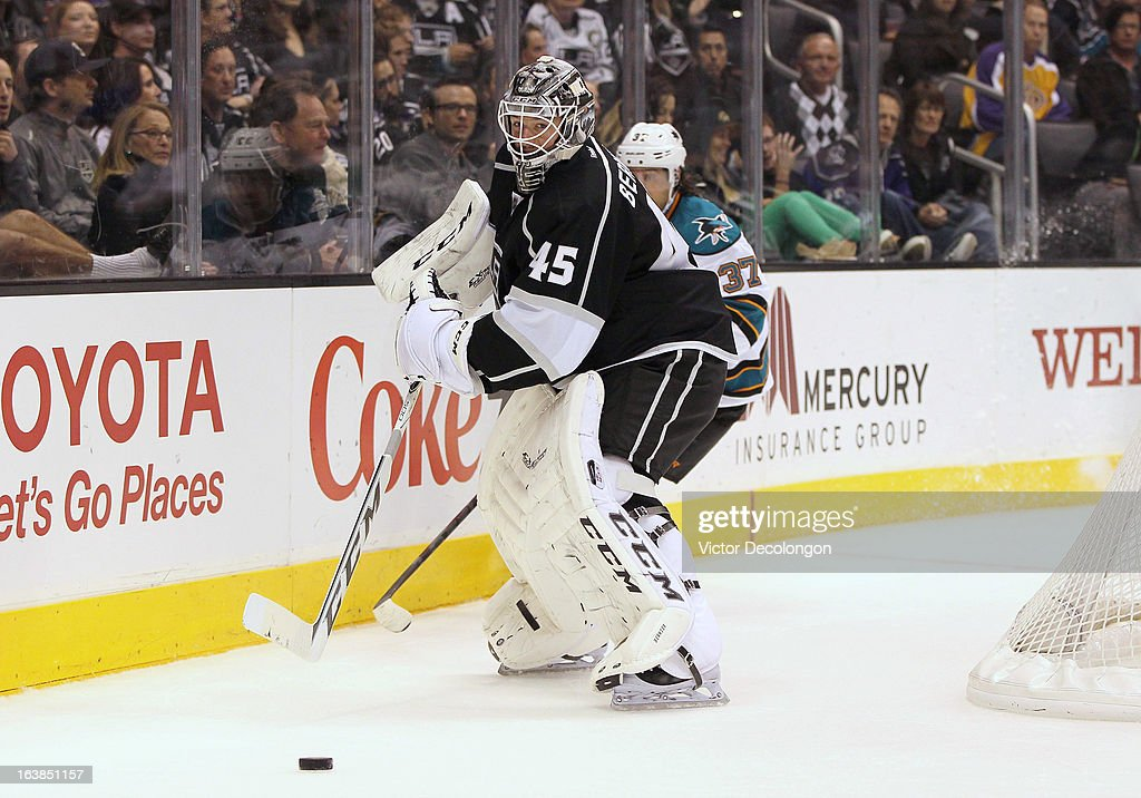 Goaltender Jonathan Bernier #45 of the Los Angeles Kings plays the puck behind the net while under pressure from Adam Burish #37 of the San Jose Sharks in the first period during the NHL game at Staples Center on March 16, 2013 in Los Angeles, California. The Kings defeated the Sharks 5-2.