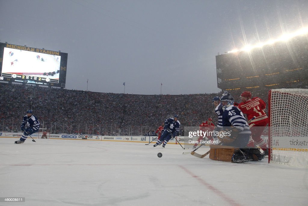 Goaltender <a gi-track='captionPersonalityLinkClicked' href=/galleries/search?phrase=Jonathan+Bernier&family=editorial&specificpeople=540491 ng-click='$event.stopPropagation()'>Jonathan Bernier</a> #45 of the Toronto Maple Leafs makes a save in overtime against the Detroit Red Wings during the 2014 Bridgestone NHL Winter Classic on January 1, 2014 at Michigan Stadium in Ann Arbor, Michigan. The Maple Leafs defeated the Red Wings 3-2 in shootout overtime.