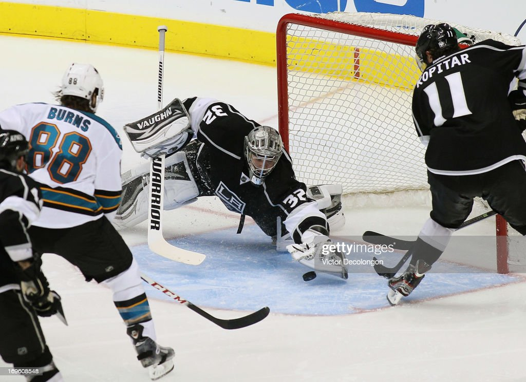 Goaltender Jonathan Quick of the Los Angeles Kings covers the puck as teammate Anzke Kopitar helps defend the Kings net while Brent Burns of the San...