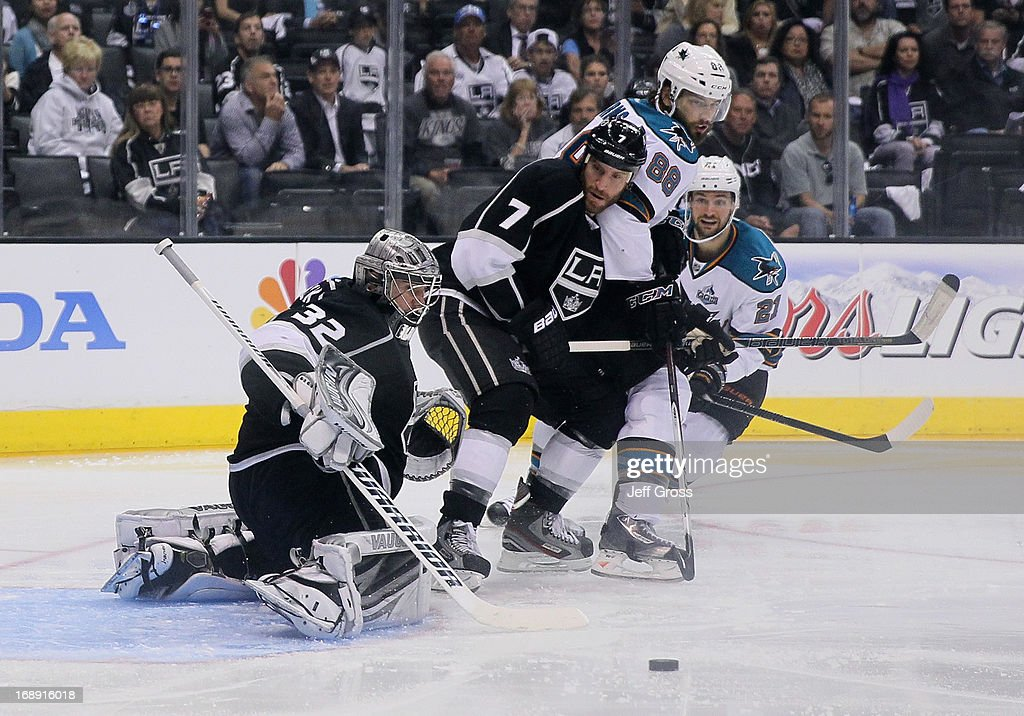 Goaltender <a gi-track='captionPersonalityLinkClicked' href=/galleries/search?phrase=Jonathan+Quick&family=editorial&specificpeople=2271852 ng-click='$event.stopPropagation()'>Jonathan Quick</a> #32 of the Los Angeles Kings makes a save, as <a gi-track='captionPersonalityLinkClicked' href=/galleries/search?phrase=Rob+Scuderi&family=editorial&specificpeople=228124 ng-click='$event.stopPropagation()'>Rob Scuderi</a> #7 of the Kings, along with <a gi-track='captionPersonalityLinkClicked' href=/galleries/search?phrase=Brent+Burns&family=editorial&specificpeople=212883 ng-click='$event.stopPropagation()'>Brent Burns</a> #88 and <a gi-track='captionPersonalityLinkClicked' href=/galleries/search?phrase=T.J.+Galiardi&family=editorial&specificpeople=4324979 ng-click='$event.stopPropagation()'>T.J. Galiardi</a> #21 of the San Jose Sharks pursue in the second period of Game Two of the Western Conference Semifinals during the 2013 NHL Stanley Cup Playoffs at Staples Center on May 16, 2013 in Los Angeles, California. The Kings defeated the Sharks 4-3.