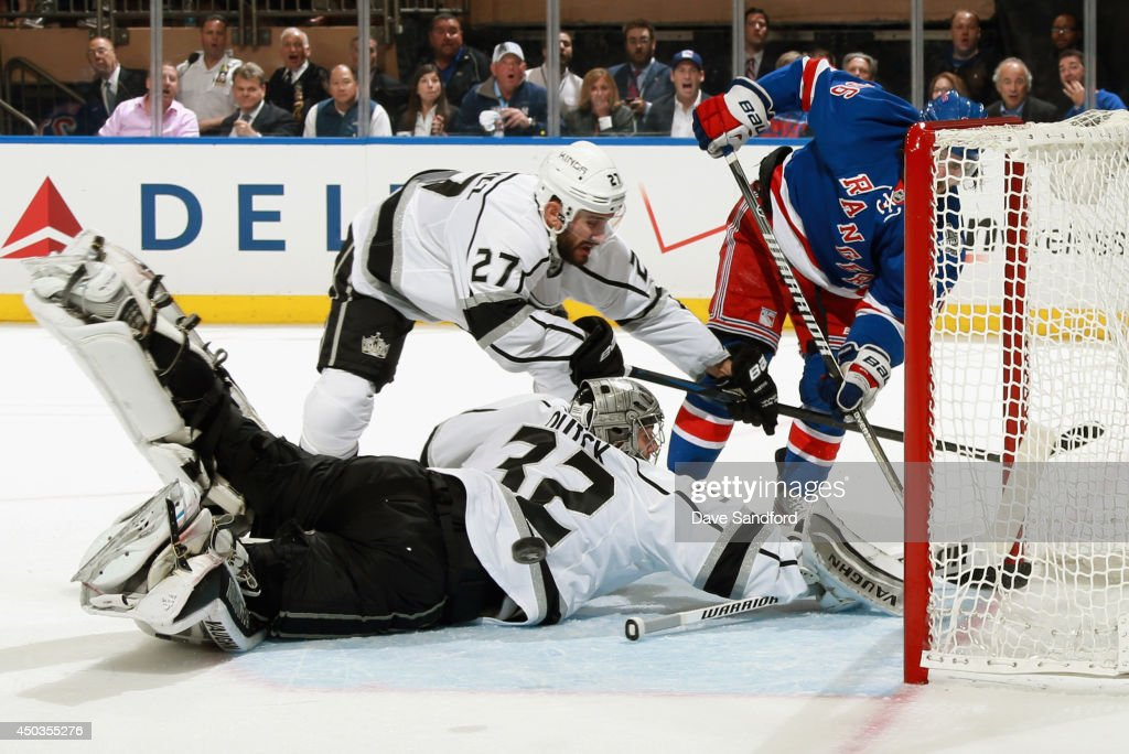 Goaltender Jonathan Quick of the Los Angeles Kings makes a save next to teammate Alec Martinez and Mats Zuccarello of the New York Rangers in the...
