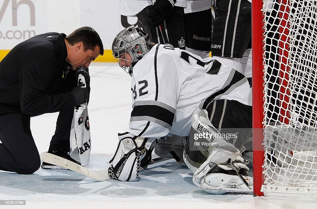 Goaltender Jonathan Quick #32 of the Los Angeles Kings speaks with a trainer before leaving the game in overtime during their 3-2 shootout loss to the Buffalo Sabres on November 12, 2013 at the First Niagara Center in Buffalo, New York.