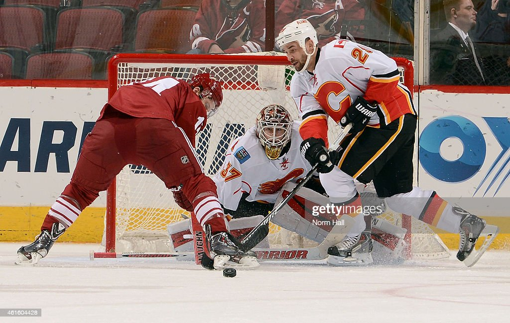 Goaltender Joni Ortio #37 of the Calgary Flames deflects the puck between Joe Vitale #14 of the Arizona Coyotes and Deryk Engelland #29 of the Flames on a save during the third period at Gila River Arena on January 15, 2015 in Glendale, Arizona.