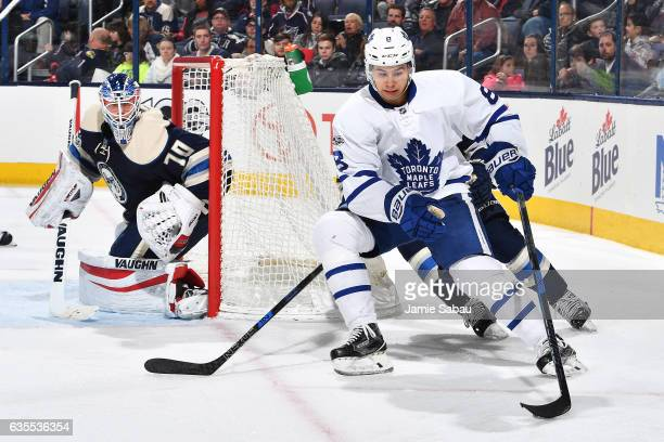 Goaltender Joonas Korpisalo of the Columbus Blue Jackets defends the net as Connor Carrick of the Toronto Maple Leafs skates with the puck during the...