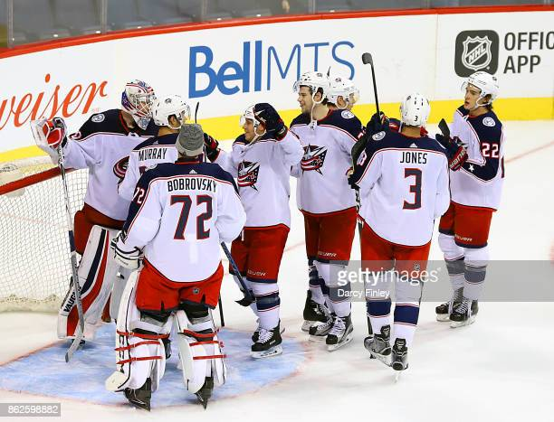 Goaltender Joonas Korpisalo of the Columbus Blue Jackets gets congratulated by teammates after backstopping the team to a 52 victory over the...