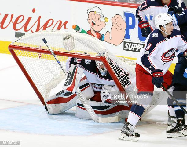 Goaltender Joonas Korpisalo of the Columbus Blue Jackets huddles in the crease as the net tips over him during second period action against the...