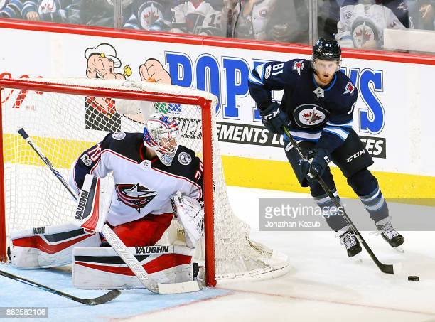 Goaltender Joonas Korpisalo of the Columbus Blue Jackets hugs the post as Kyle Connor of the Winnipeg Jets plays the puck around the net during...