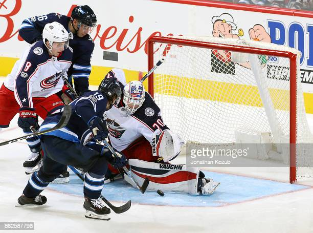 Goaltender Joonas Korpisalo of the Columbus Blue Jackets makes a pad save on Nic Petan of the Winnipeg Jets during second period action at the Bell...
