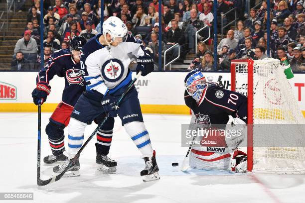 Goaltender Joonas Korpisalo of the Columbus Blue Jackets stops a shot as Jack Johnson of the Columbus Blue Jackets and Joel Armia of the Winnipeg...
