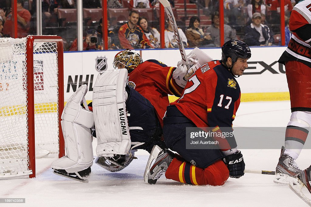 Goaltender Jose Theodore #60 falls over Filip Kuba #17 of the Florida Panthers as he attempts to get back into the net against the Carolina Hurricanes during the seasons opener at the BB&T Center on January 19, 2013 in Sunrise, Florida.The Panthers defeated the Hurricanes 5-1.