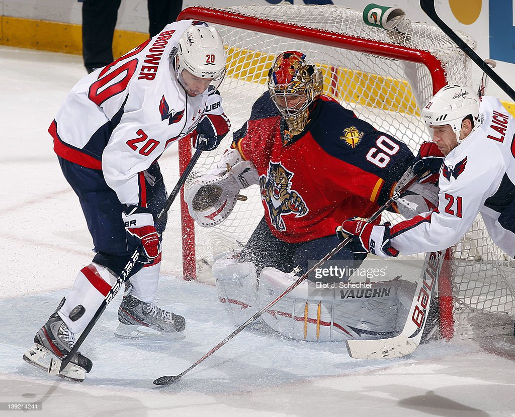 Goaltender Jose Theodore #60 of the Florida Panthers defends the net against Troy Brouwer #20 of the Washington Capitals and teammate Brooks Laich #21at the BankAtlantic Center on February 17, 2012 in Sunrise, Florida.