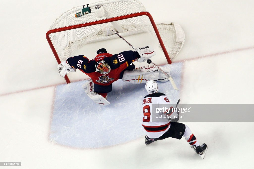 Goaltender Jose Theodore of the Florida Panthers defends the net against Zach Parise of the New Jersey Devils in Game One of the Eastern Conference...