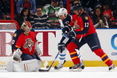 Goaltender Jose Theodore of the Florida Panthers defends the net with the help of teammate Filip Kuba against Olli Jokinen of the Winnipeg Jets at...