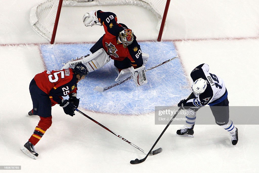 Goaltender Jose Theodore #60 of the Florida Panthers defends the net with the help of teammate Jerred Smithson #25 against Andrew Ladd #16 of the Winnipeg Jets at the BB&T Center on January 31, 2013 in Sunrise, Florida.