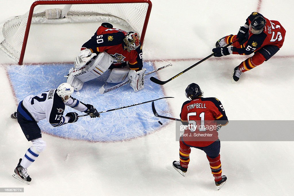 Goaltender Jose Theodore #60 of the Florida Panthers defends the net with the help of teammates and Brian Campbell #51 and Marcel Goc #57 against Olli Jokinen #12 of the Winnipeg Jets at the BB&T Center on January 31, 2013 in Sunrise, Florida.