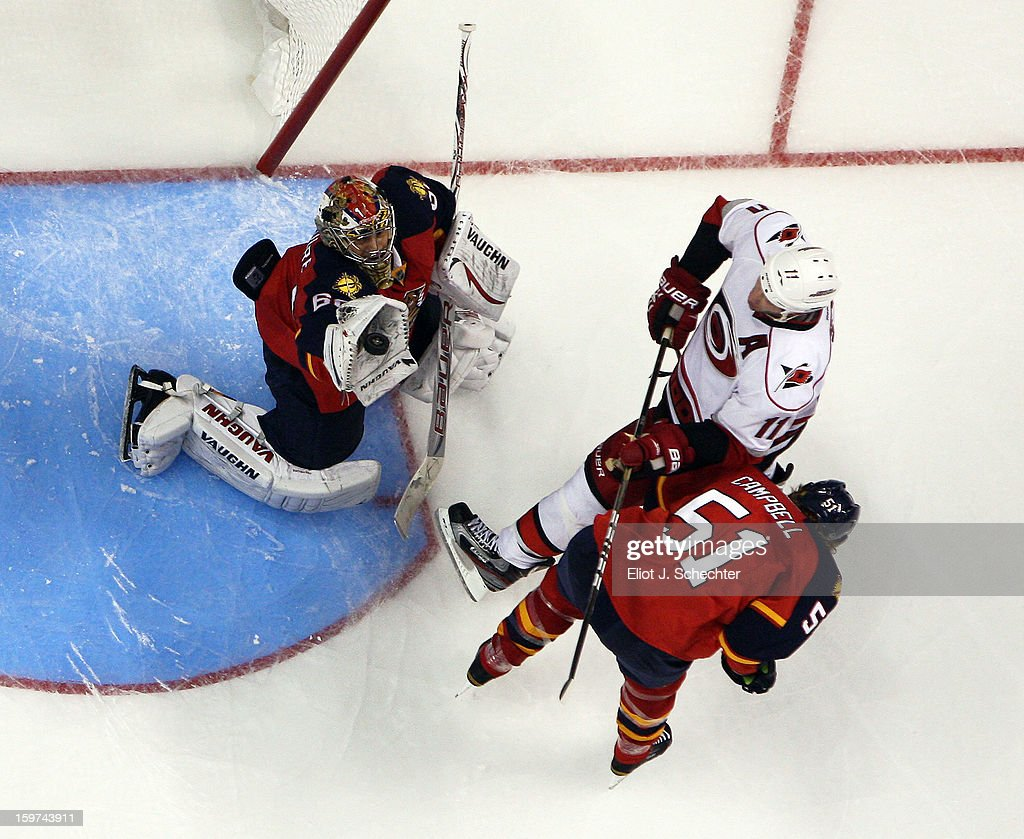 Goaltender Jose Theodore #60 of the Florida Panthers makes a glove save with the help of teammate Brian Campbell #51against Jordan Staal #11 of the Carolina Hurricanes at the BB&T Center on January 19, 2013 in Sunrise, Florida.