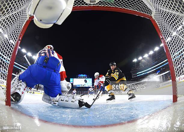 Goaltender Jose Theodore of the Montreal Canadiens Alumni Team makes a save on Mark Recchi of the Boston Bruins Alumni Team during the Alumni Game as...