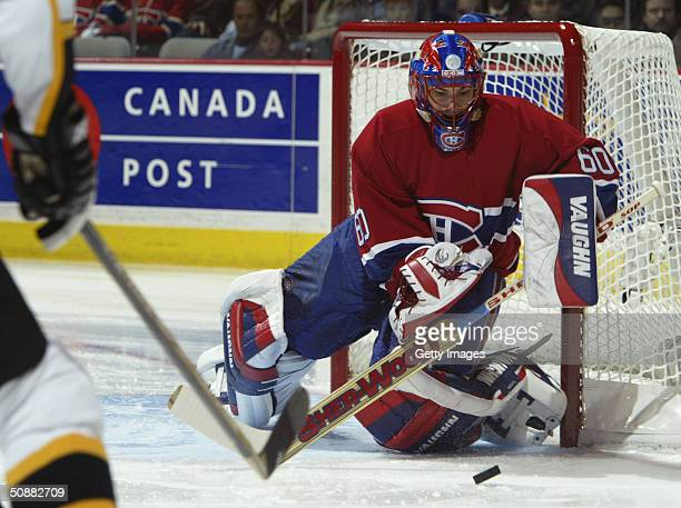 Goaltender Jose Theodore of the Montreal Canadiens looks to knock the puck away from the front of the net during game four of the 2004 NHL Eastern...