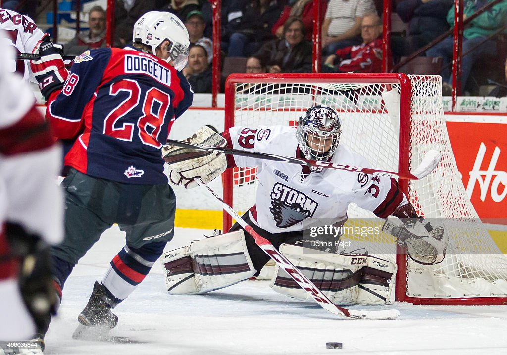 Goaltender Justin Nichols #39 of the Guelph Storm dives for the puck against forward Slater Doggett #28 of the Windsor Spitfires on March 12, 2015 at the WFCU Centre in Windsor, Ontario, Canada.