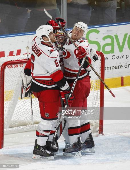 Goaltender Justin Peters is congratulated by Tim Gleason and Joe Corvo of the Carolina Hurricanes after defeating the Florida Panthers on December 15...